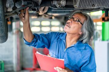 Senior Man Mechanic Examining Under the Car at the Repair Garage.