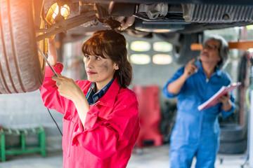 Senior Man and Woman Mechanic Examining Under the Car at the Repair Garage.