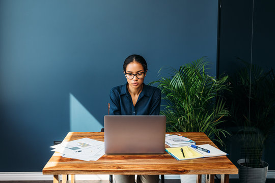 Serious woman sitting at a table and working remotely on a laptop from home