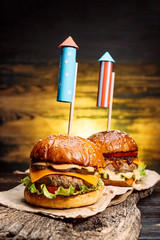 close up Image of two beef burgers with fireworks rockets. picnic festive snack on the fourth of july independence day
