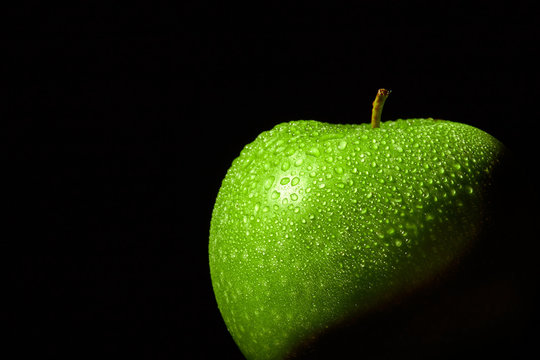 Fresh green apple with water droplets on black background. Close-up macro photo concept for green fruits, freshness, healthy nutrition. Conceptual background.