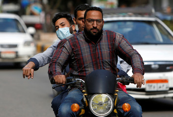 A man wearing protective face mask rides a motorbike in Cairo