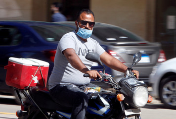 A man wearing a protective face mask rides a motorbike in Cairo