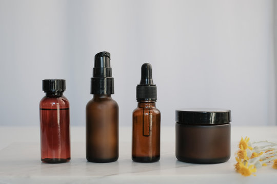 set of amber glass cosmetic skincare packaging . blank and no label with flower.