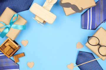 Fathers Day themed frame of ties, gifts and games on a blue background. Top view with copy space.