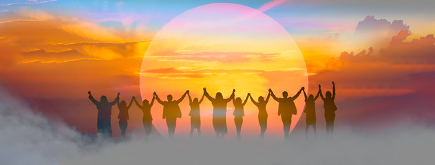 Business people holding and raised arms together on teamwork with sunrise background.  Fotobehang