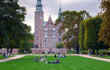 People lie on the grass, relaxing and walking around green park near Rosenborg Castle, built in 17th century