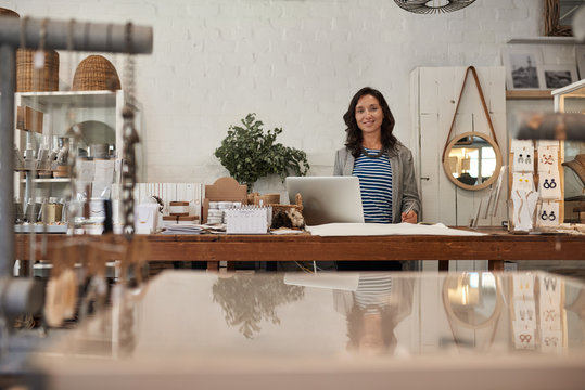 Smiling Asian woman working behind a counter in her shop
