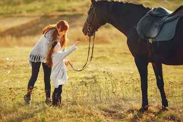 Mother and daughter next to horse. Little girl in a summer field. Family playing with a horse Papier Peint