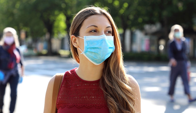 COVID-19 Social Distancing Woman in city street wearing surgical mask against disease virus SARS-CoV-2. Girl with face mask walks respecting social distancing during Pandemic Coronavirus Disease 2019.