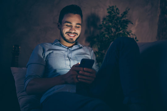 Portrait of his he nice attractive cheerful cheery brunet guy sitting on divan using digital device late night flirting pastime at modern loft industrial style interior dark room apartment flat indoor