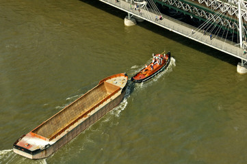 Empty barge on the Thames heading under the Golden Jubilee Bridge, London, England