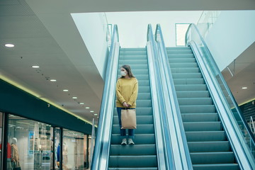 lone woman in a protective mask standing on the escalator steps