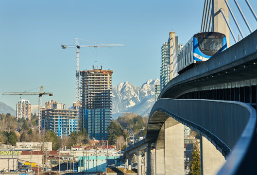 Urban Growth Vancouver. Modern towers grow along Vancouver's skyline behind a rapid transit line. British Columbia, Canada.