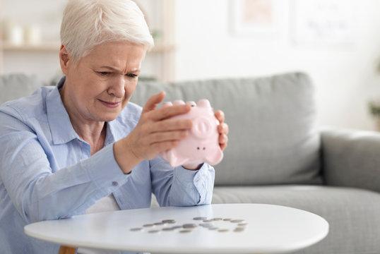 Financial Crisis. Sad Senior Woman Shaking Piggy Bank, Taking Out Coins