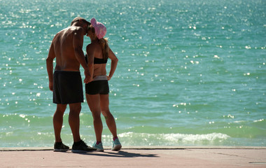 A couple share a kiss as sun-seekers return to the beach during a phased reopening  in St. Pete Beach