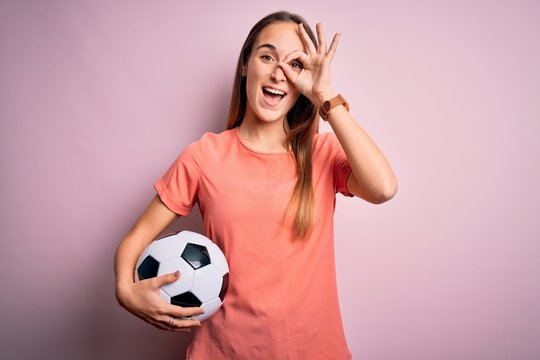 Young beautiful player woman playing soccer holding football ball  over pink background with happy face smiling doing ok sign with hand on eye looking through fingers