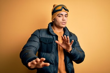 Young brazilian skier man wearing snow sportswear and ski goggles over yellow background Moving away hands palms showing refusal and denial with afraid and disgusting expression. Stop and forbidden.