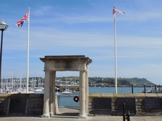 Gate And British Flags Against Boats Moored At Barbican Harbor