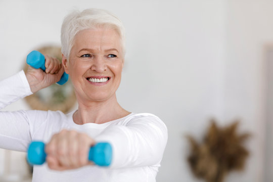 Closeup Portrait Of Elderly Woman Doing Exercises With Dumbbells At Home