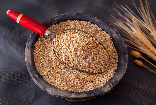 Uncooked steel cut oats in a rustic bowl