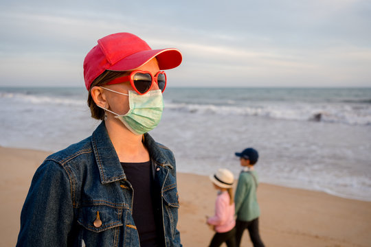 Beautiful woman wearing medical mask at the beach sunset sky natural outdoor background. Covid19 sanitary measures, paranoia prevention. Free personal alert. Holiday traveling freedom bliss