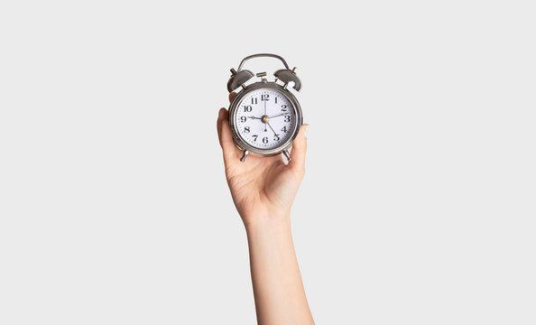 Time optimization concept. Female hand holding alarm clock on light background, close up