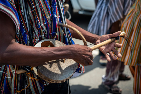 A street musician plays a traditional African Lute also known as a Pluriarc as he marches in a festival celebration parade in Ghana, West Africa.