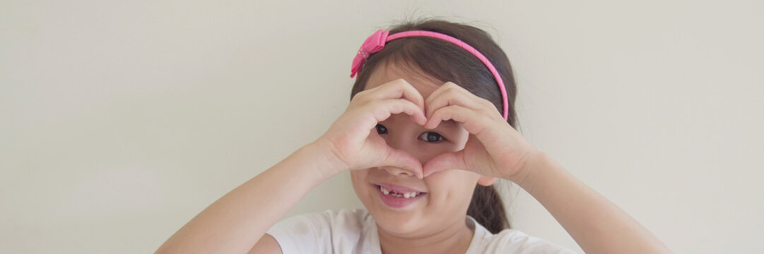 Mixed Asian girl making heart shape hands through eyes, Generous, love and kindness, sustainable living, donate, charity, young volunteer concept