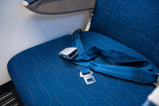 An unfastened seat belt on an empty seat in an airplane. Safety in flight