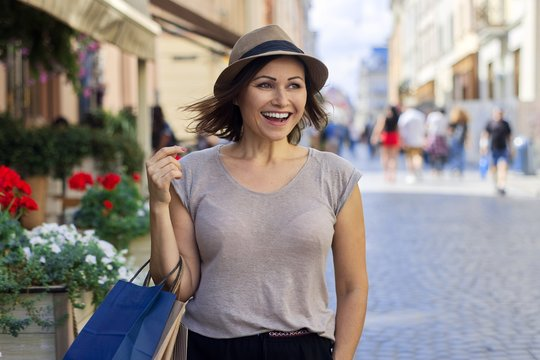 Portrait of mature beautiful successful smiling woman in hat with shopping bags