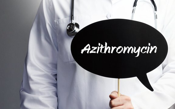Azithromycin. Doctor in smock holds up speech bubble. The term Azithromycin is in the sign. Symbol of illness, health, medicine