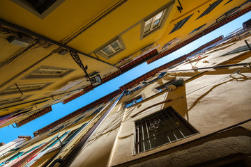 Narrow street view from the bottom up to the sky