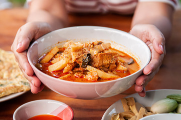 Thai local homemade food red curry with chicken in ceramic bowl at dinner table