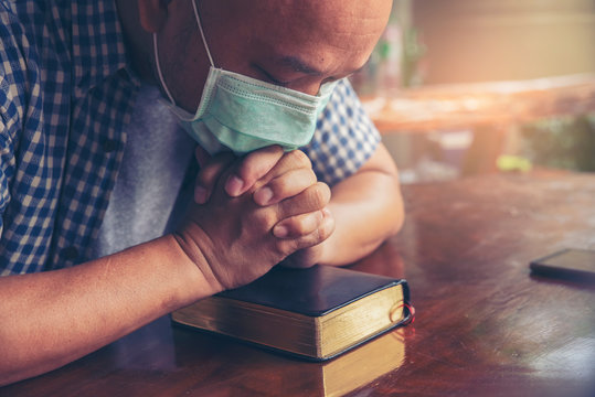 Prayer and bible concept. Asian male were medical mask praying, hope for peace and free from coronavirus, Hand in hand togethe, believes and faith in christian religion at church.
