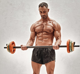 Shirtless adult male bodybuilder doing a biceps exercise with a barbell in a bright studio