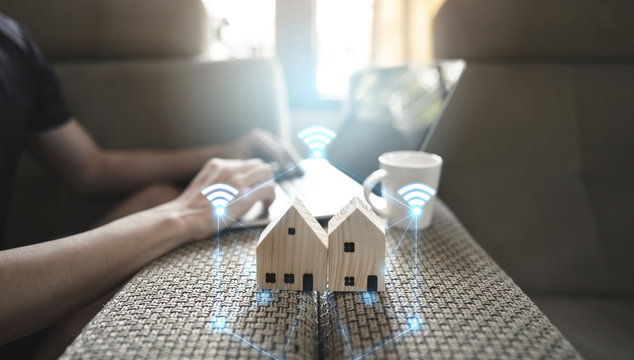 Modern lifestyle work and stay at home concept. Wooden house model with wifi internet icon.
