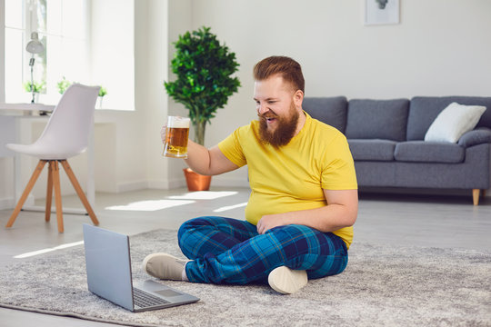 Online conference video call chat. Online party with friends. Funny man holds a glass with beer, communicates with friends video chat call online at home.