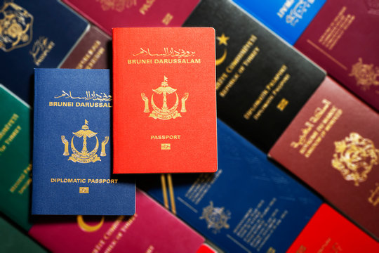 Diplomatic and national passports of Brunei Darussalam on a blurred background of different passports of world.