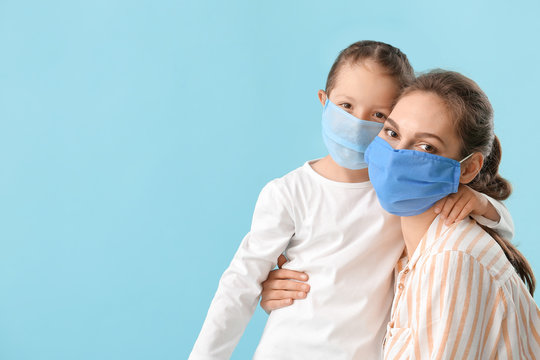 Little daughter with her mother in protective masks on color background