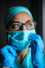 Woman doctor adjusting her surgical mask and glasses