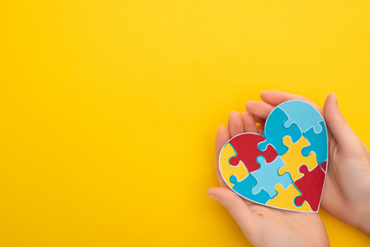 partial view of woman holding colorful puzzle heart on yellow for World Autism Awareness Day