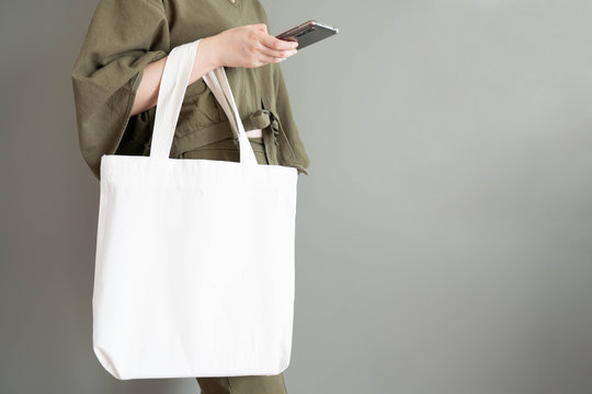 Blank white tote bag canvas fabric with handle mock up design. Close up of woman holding eco or reusable shopping bag and using smartphone near grey wall. No plastic bag and ecology concept.