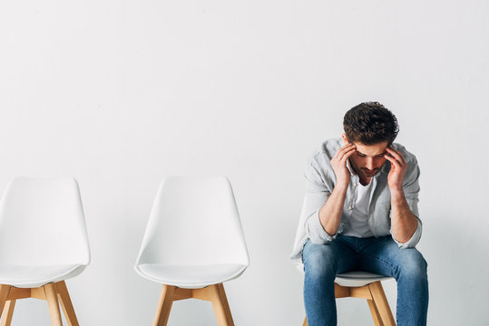 Thoughtful man waiting for job interview on chair in office