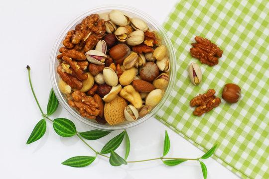Pistachio nuts, walnuts, cashew nuts, hazelnuts, peanuts, almonds in plastic box on checkered cloth