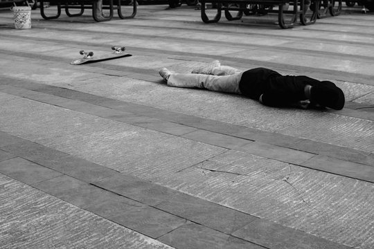 Man With Skateboard Lying Outdoors