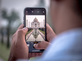 tourist taking a picture of the Taj Mahal in India