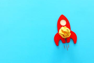 education or innovation concept. Wooden rocket over blue background
