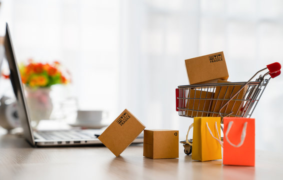 Online shopping concepts - Product package boxes in cart and laptop on desk with copy space