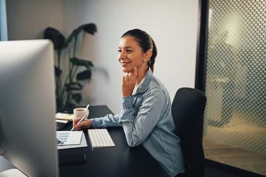 Smiling businesswoman going over paperwork and working on a comp